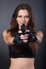 Beautiful sexy police girl with handgun and  isolated on grey ba