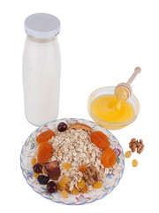 Oat flakes with fruits, honey and milk, isolated on a white