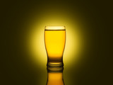 A glass of beer isolated on a dark and yellow background