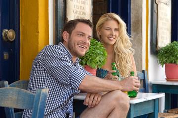 Sommer: Junges Paar sitzend im Straßencafe im Urlaub