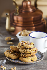 Küchentisch mit Kupferkessel, Kaffeebecher und Keksen