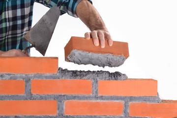 Constructor sujetando un ladrillo construyendo un muro.