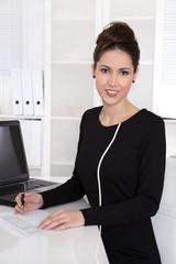 Elegante erfolgreiche junge Business Frau sitzend im Büro