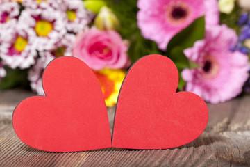 Zwei roten Herzen mit buntem Blumenstrauß im Hintergrund