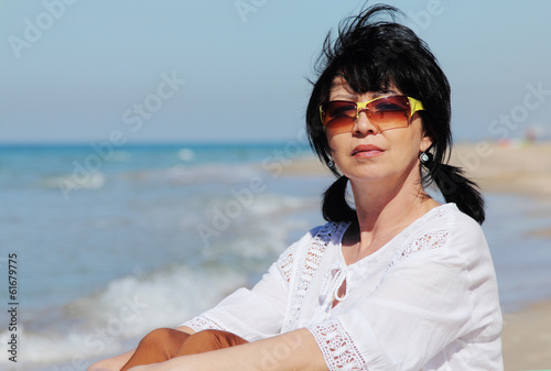 Beautiful 49 years old woman walking on the beach