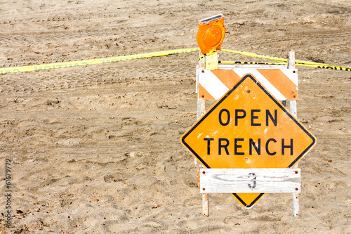 Construction site barrier, open trench warning sign in sand