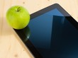 digital tablet pc and green apple on wood table