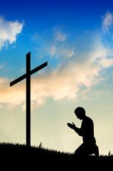 man praying under the cross