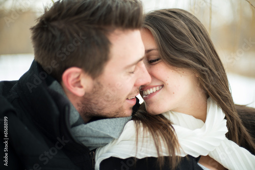 Attractive heterosexual couple kissing on a blanket in the snow