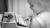 Cute Baby Girl Writing a Book on a Vintage Typewriter,