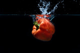 sweet pepper drop into water on black background.