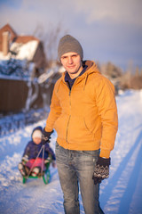 Young father sledding his little daughter on a sled in the snow