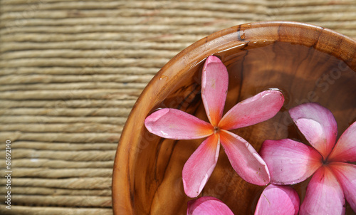 Three frangipani in water wooden bowl on Brown straw mat