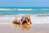 couple lying on the beach and shows heart symbol