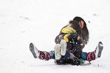 Two sisters sledging holding each other