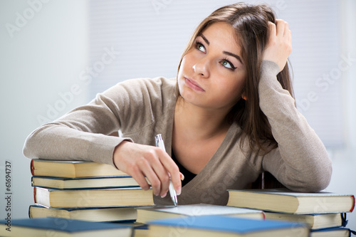 Tired student sitting with many books