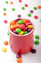 A glossy red jar with mini colorful candies