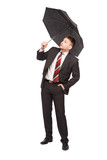 Businessman with umbrella looking up