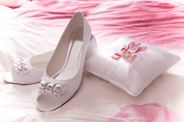 white shoes of bride with wedding rings
