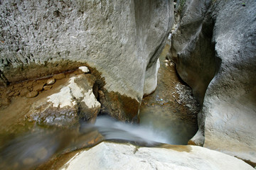 A small waterfall and flowing water and form some narrow gorges