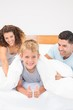 Cute young family messing about on bed