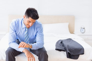 Handsome businessman sitting on bed checking the time