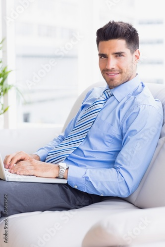Businessman on couch using his laptop smiling at camera
