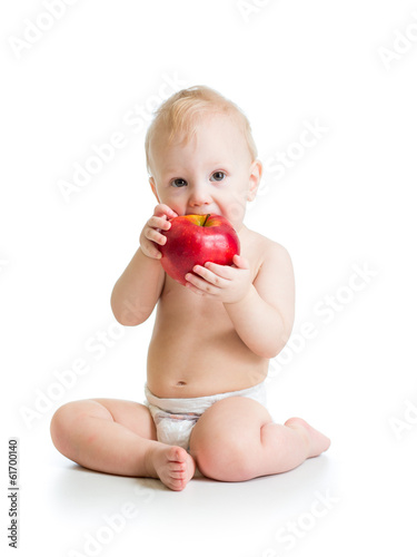 Baby boy eating red apple, isolated on white