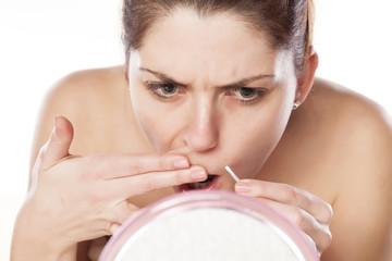 woman remove hair from her mustache using tweezers