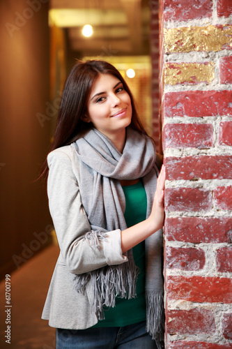 Young happy woman standing near the brick wall