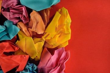 Colorful group of paper balls on red paper background.