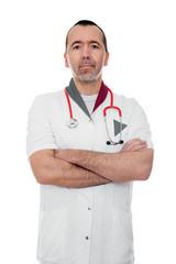 Arzt mit verschränkten Armen sieht zum Betrachter