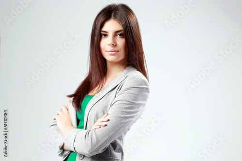 Portrait of a young woman with arms folded on gay background