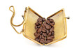 Golden purse with coffee beans isolated on white