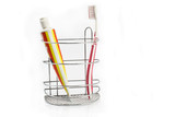 Toothbrush beside toothpaste in metal holder  isolated on white