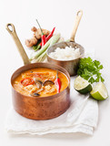 Spicy Thai soup Tom Yam with Rice, Chili pepper and Seafood on w