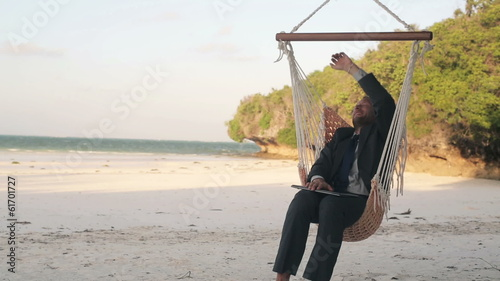 Businessman finishing work on laptop, relaxing on hammock