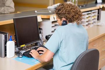 Nurse Answering Telephone While Working On Computer At Reception