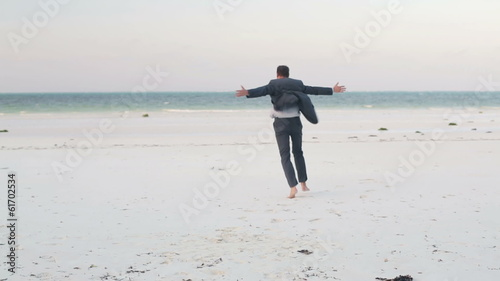 Excited, happy businessman running on exotic beach,