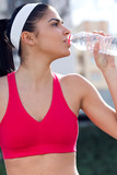 Young athlete drinking water after exercise