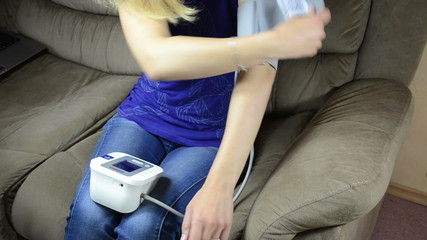 Woman measuring blood pressure take off measure tool from hand
