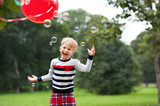 Laughing little blonde girl playing with soap bubbles in park