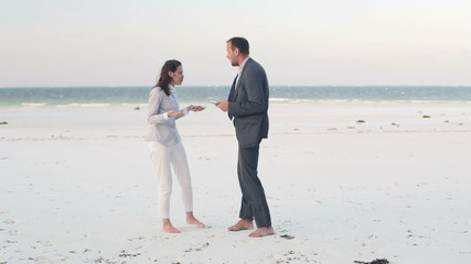 Lost business couple fighting over tablet on exotic beach