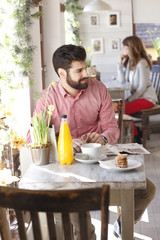 Modern young man sitting in coffee shop