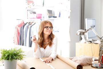 Beautiful fashion designer working in her studio