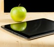 tablet pc and green apple in front of blackboard on wood table