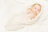 newborn baby covering in soft woolen blanket, white background