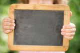 Child holding blackboard