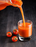 Tomato juice pouring from jug into a glass