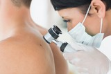 Dermatologist examining mole on patient poster